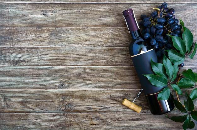 Бутылка с красным вином, штопором, синим виноградом, листьями на деревянном столе. Premium Фотографии