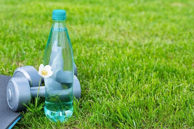 Бутылка с водой, гантелями и ковриком для занятий спортом и йогой на зеленой траве. копировать пространство Premium Фотографии
