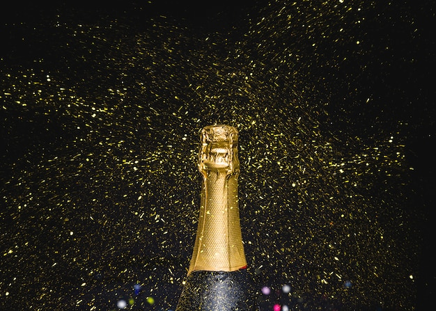 Bottleneck of champagne with flying glitters Free Photo