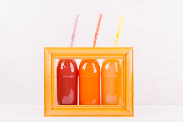 Bottles of colorful juice in frame Free Photo