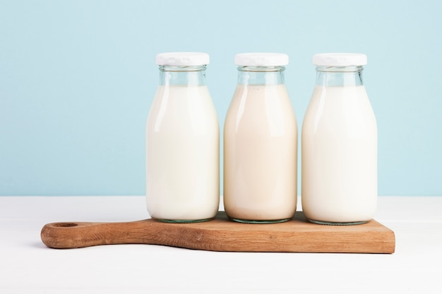 Bottles filled with milk on chopping board Free Photo