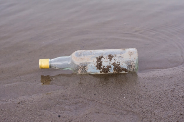 Bottles and garbage waste on the shore of a river. Premium Photo