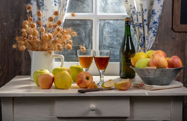 Bottles and glasses of cider with apples on the table. in rustic house Premium Photo