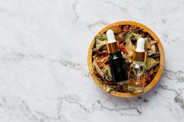 Bottiglie di olio di trattamento termale a base di erbe messe in una ciotola di legno Foto Gratuite