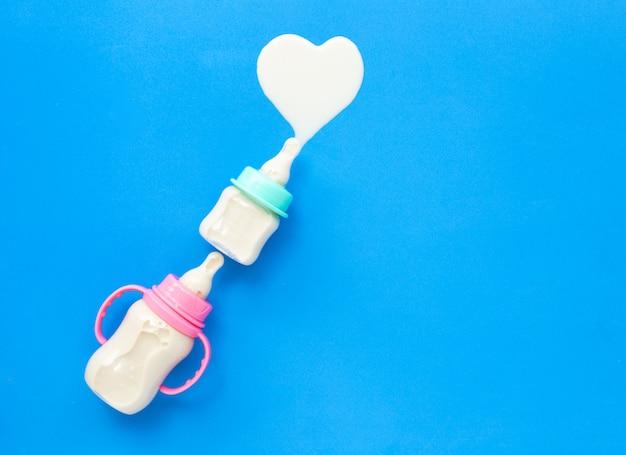 Bottles of milk for baby on blue surface. milk heart shape Premium Photo
