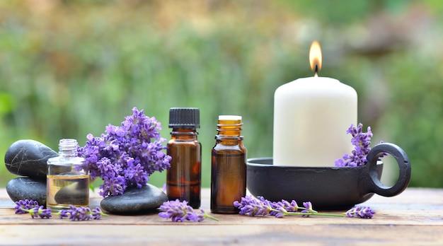 庭の木製のテーブルの上に配置されたラベンダーの花の中でエッセンシャルオイルのボトル Premium写真