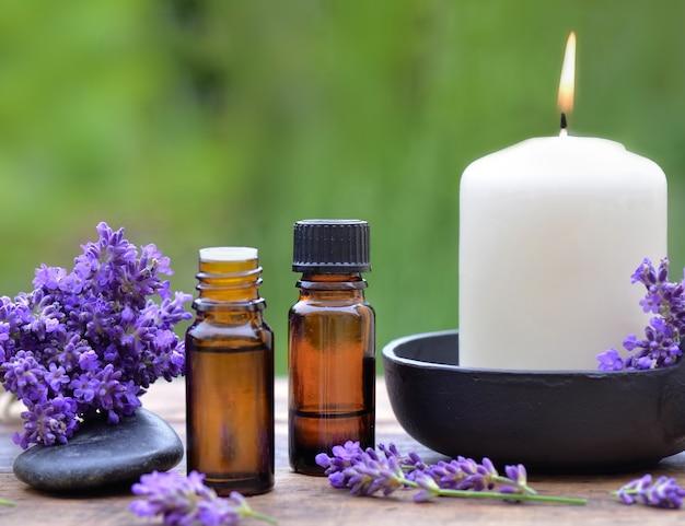 エッセンシャルオイルとキャンドルと木製のテーブルの上に配置されたラベンダーの花の花束のボトル Premium写真