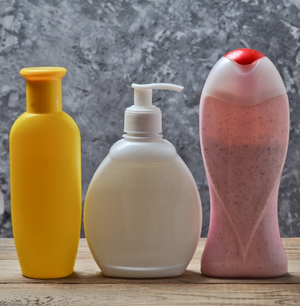 Bottles of products for a shower on a wooden shelf against a gray concrete wall. shower gel, shampoo, liquid soap. Premium Photo