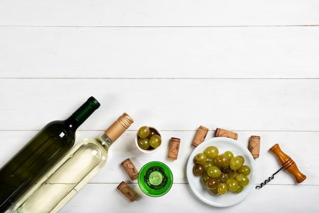 Bottles of white wine next to corks and grapes Free Photo