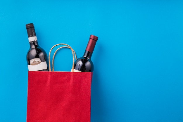 Bottles of wine in red shopping bag against blue wallpaper Free Photo