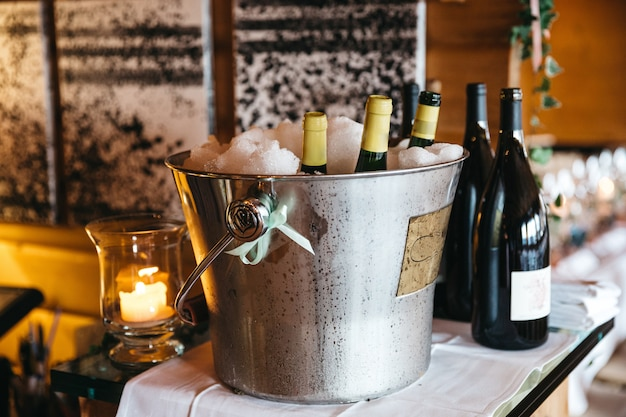 Bottles with champagne are cooling in pail with ice and bottles with wine are near Free Photo