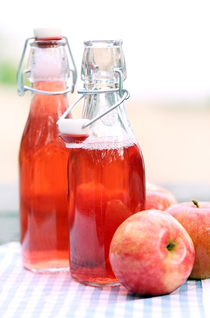 Bottles with red drinks and some apples Free Photo