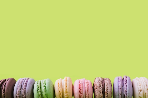 Bottom border made with colorful macaroons on green backdrop Free Photo