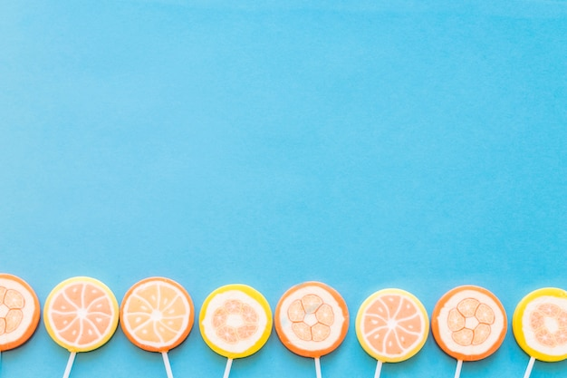 bottom border of jelly lollipops over blue background photo free