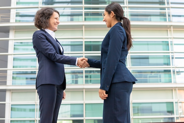 Bottom view of cheerful colleagues shaking hands near building. young women wearing formal suits meeting outdoor. business handshake concept Free Photo