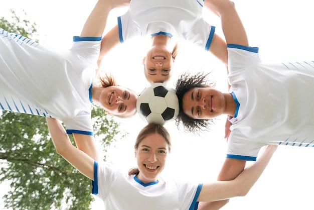 Vista dal basso donne felici che tengono palla Foto Gratuite