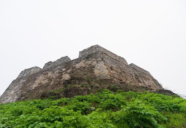 Вид снизу на оборонительную каменную крепость замка. Premium Фотографии