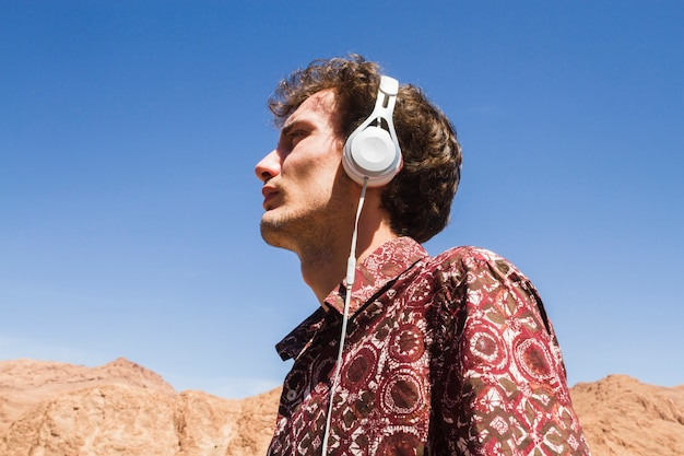 Bottom view portrait of man listening to music in desert Free Photo