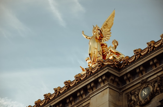 Bottom view shot of the golden statue of a woman with wings in paris, france Free Photo