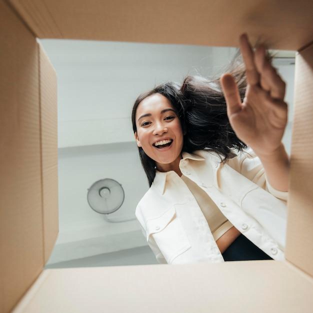 Donna di smiley vista dal basso alla ricerca su una scatola Foto Gratuite