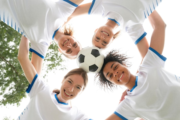 Donne di smiley vista dal basso che tengono palla Foto Gratuite