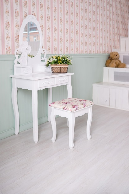 Boudoir table. details of the interior of the bedroom for girls and make-up, hairstyles with a mirror. Premium Photo