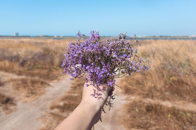 Bouquet of beautiful purple flowers in woman's hand Premium Photo