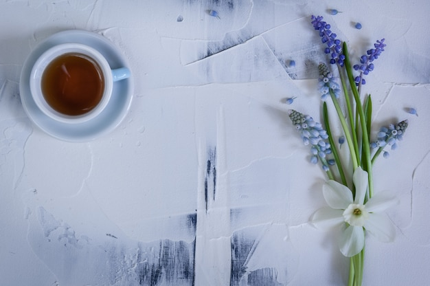 Bouquet of blue muscaries flowers and cup of tea on white background. Premium Photo