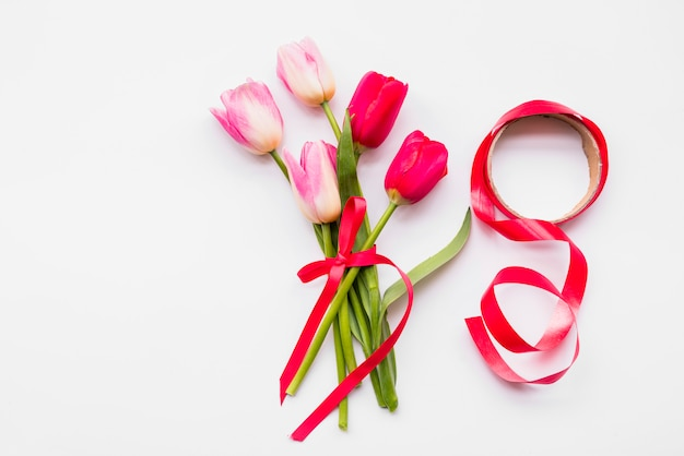 Bouquet of bright fresh flowers on stems near roll of ribbon Free Photo