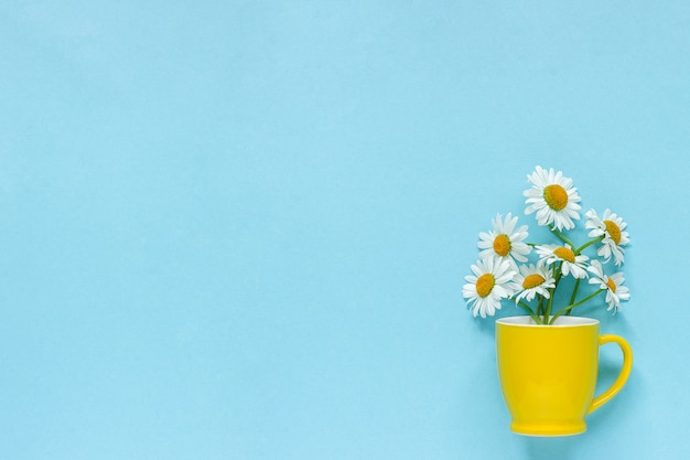 Bouquet chamomile daisies flowers in yellow mug on pastel blue background Premium Photo