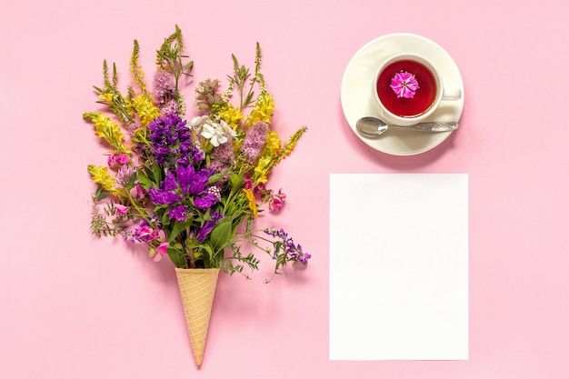 Bouquet colored flowers in ice cream waffle cone, cup of tea and blank paper card Premium Photo