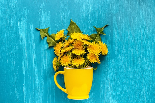 Bouquet dandelions taraxacum flowers in yellow mug Premium Photo