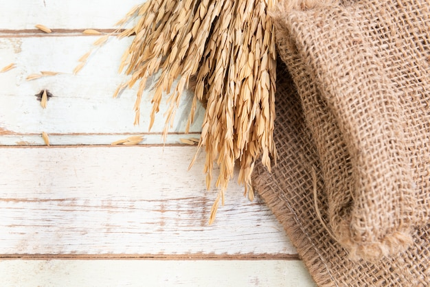 Bouquet dry ears of rice thai jusmine and burlap or sackcloth on wood table.,top view Premium Photo