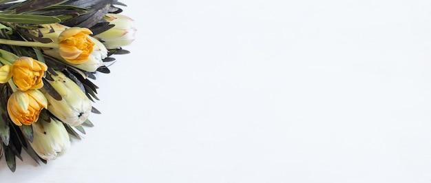 Un bouquet di fiori esotici protea e tulipani per la vista dall'alto della vacanza. consegna dei fiori e concetto di bouquet festivo. Foto Gratuite