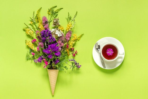 Bouquet field colored flowers in ice cream cone, cup of tea on green paper background Premium Photo