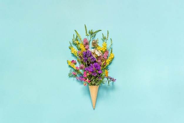 Bouquet field colored flowers in waffle ice cream cone on blue paper background Premium Photo