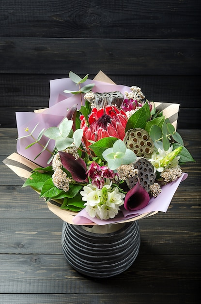 A bouquet of flowers on a dark wooden background. bouquet with protea, orchid, poppy, succulent.. Premium Photo