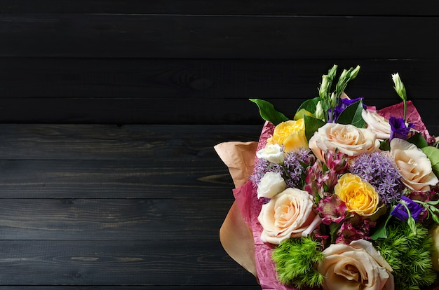 A bouquet of flowers on a dark wooden background. bouquet with roses. Premium Photo