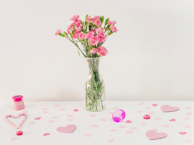 Bouquet of flowers in vase near set of paper hearts and candy canes Free Photo