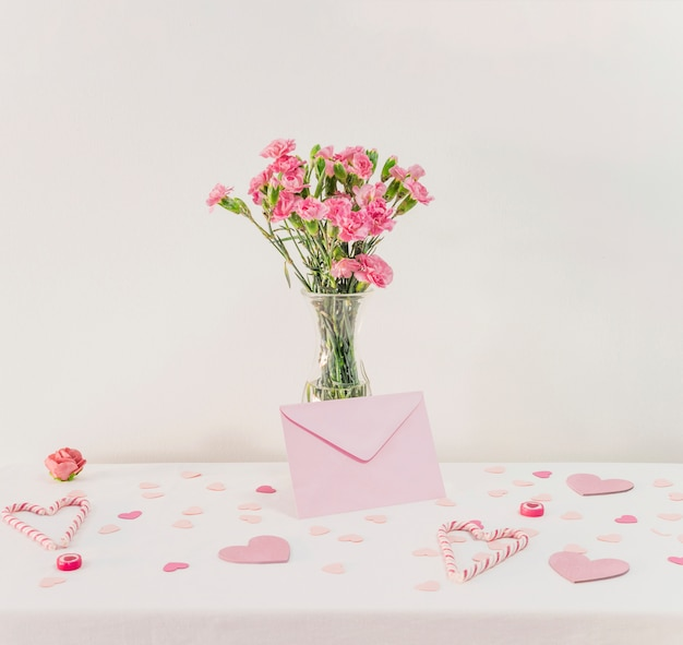 Bouquet of flowers in vase near set of paper hearts, envelope and candy canes Free Photo