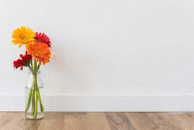 Bouquet of flowers in vase near wall Free Photo