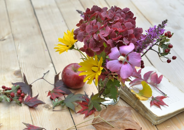 Bouquet of flowers with beautiful autumnal colors on a table in leaves Premium Photo