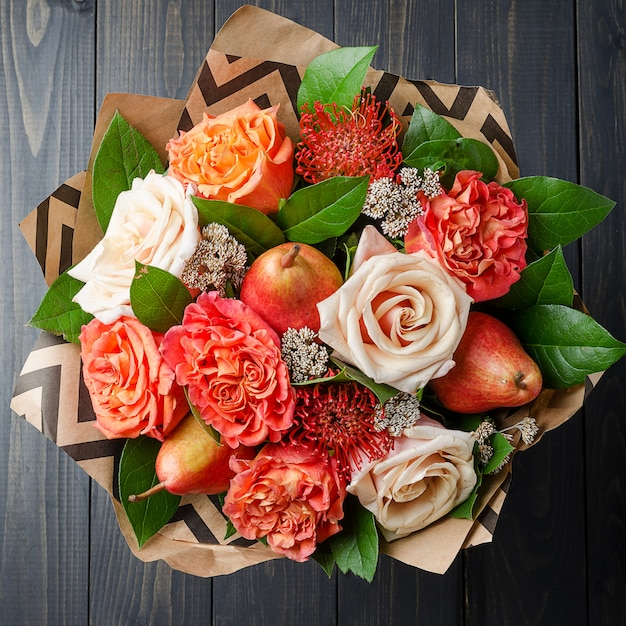 Bouquet of flowers with pears on a dark wooden background. fruit bouquet. Premium Photo