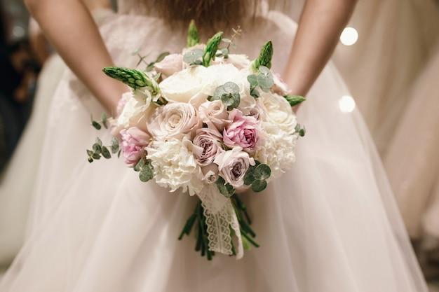 彼女は結婚式の店で白いウェディングドレスを着ている花嫁によって保持されている花束。顔のない写真 Premium写真