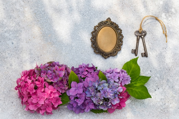 A bouquet of hydrangeas, an old frame for photos and keys Premium Photo