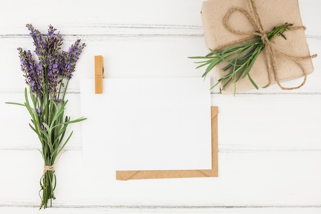 Bouquet of lavender flower; white paper and wrapped present box on wooden table Premium Photo