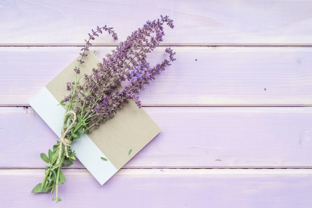 Bouquet of lavender flowers on closed notebook over the purple background Free Photo