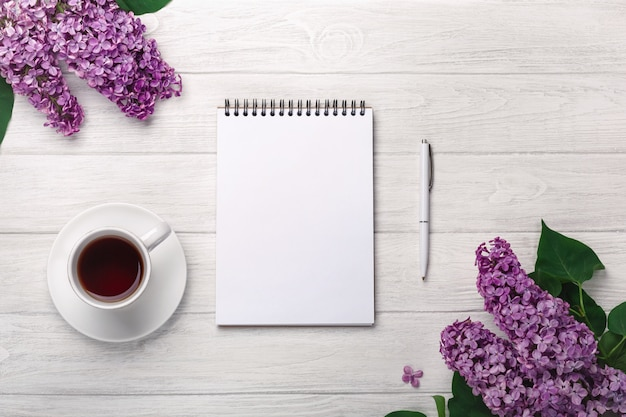 A bouquet of lilacs with cup of tea, notebook, craft envelopes on white boards . mother's day Premium Photo