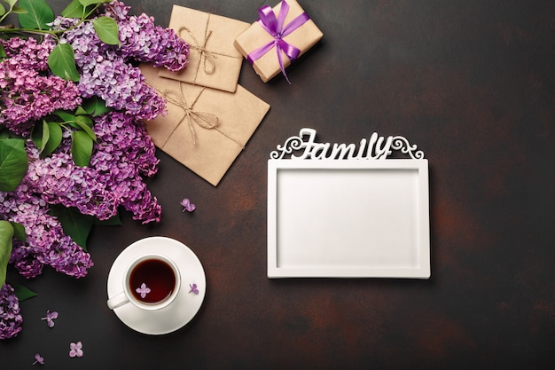 A bouquet of lilacs with cup of tea, a white frame for inscription, gift box, craft envelope, a love note on rusty background Premium Photo