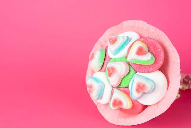 Bouquet of marmalade and sweets in pink packaging on a pink background Premium Photo